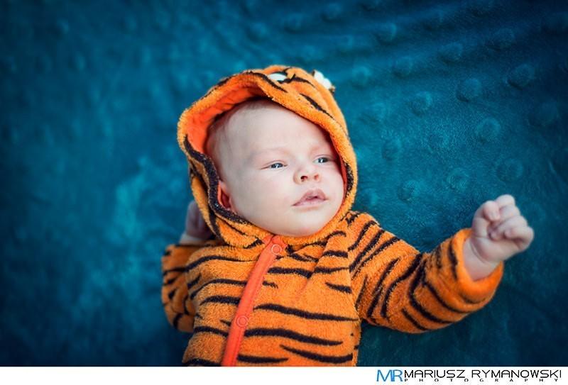 Zdjęcie maluszka na błękitnym kocyku w stroju tygryska