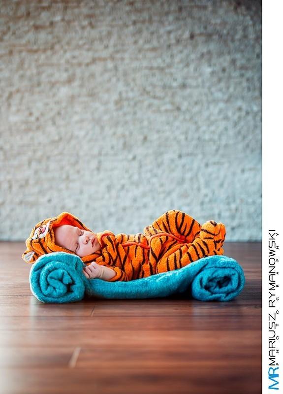 Zdjęcie dziecka s stroju tygryska na tle białej sciany