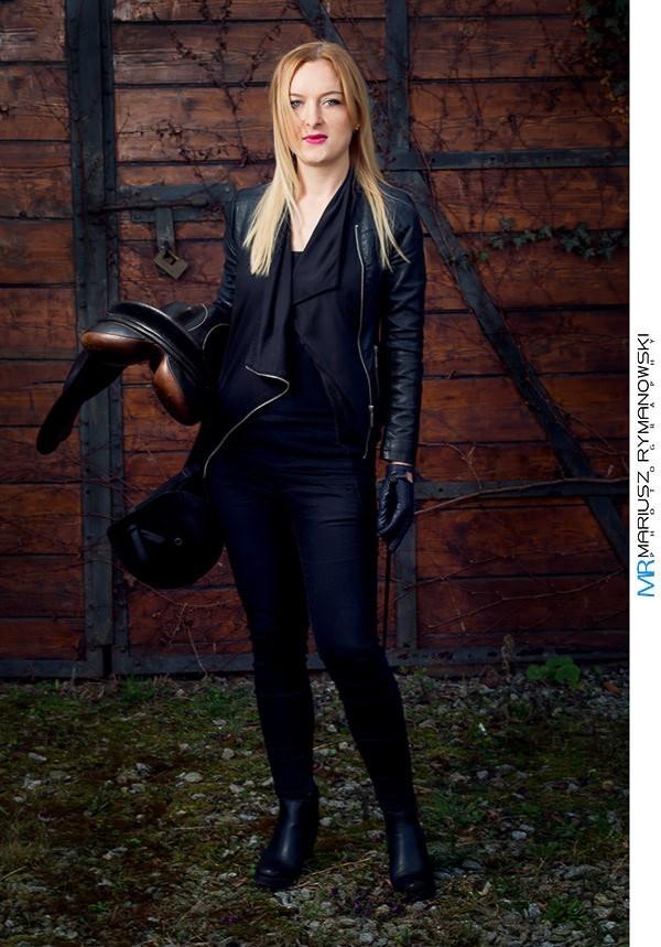 Kobieta w stroju jeżdzieckim trzymająca siodło